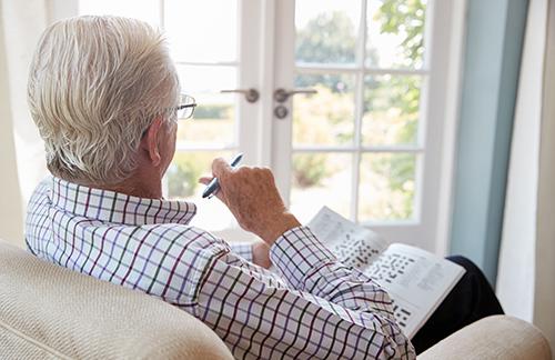 Elderly gentleman doing crossword