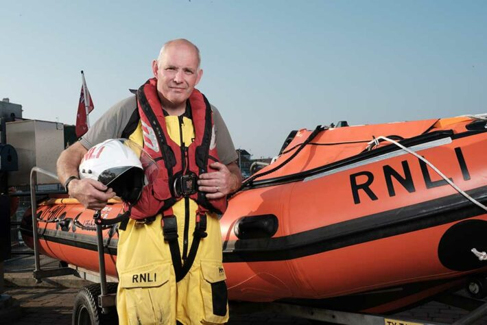 Keith next to an RNLI boat ready for launch telling his diabetic foot ulcer story