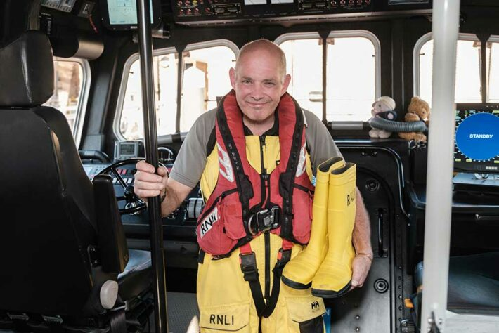 Keith with his wellies onboard an RNLI boat